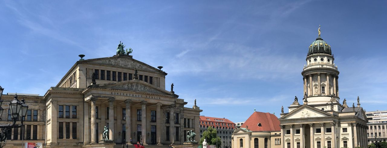 Panoramic view of franzosischer dom and konzerthaus berlin against blue sky