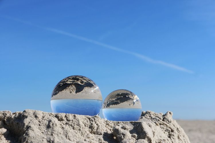 two crystal balls are lying in the sand at the beach Crystal Ball Decor EyeEm Best Shots EyeEm Nature Lover Germany🇩🇪 Mirror Reflection Tourisme Ball Balls Beach Blue Clear Sky Close-up Crystal Day Lying Down Nature No People North Sea Northsea Outdoors Sand Sky