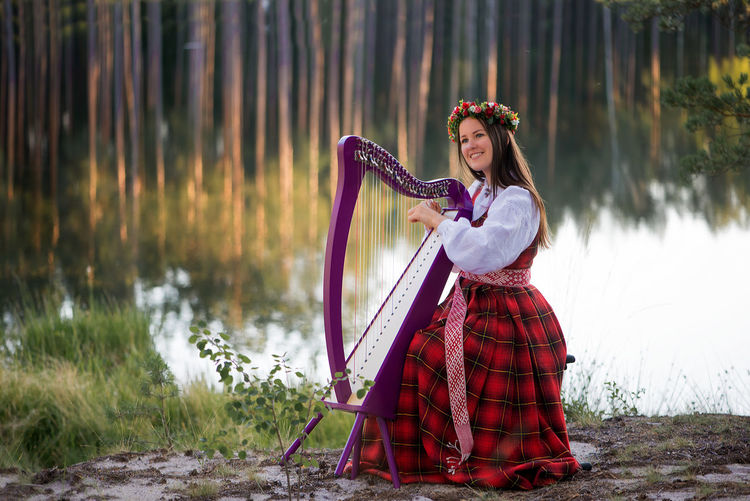 A beautiful woman in a Latvian national costume playing a Celtic harp Folk Costume Beautiful Woman Beauty Beauty In Nature Celtic Harp Day Fashion Folk Music Forest Full Length Lake Lifestyles National Costume Nature One Young Woman Only Outdoors People Portrait Real People Smiling String Instrument Tree Water Young Adult Young Women Business Stories