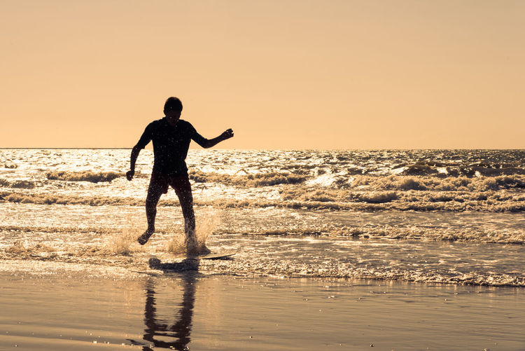 Silhouette man running in sea against clear sky during sunset