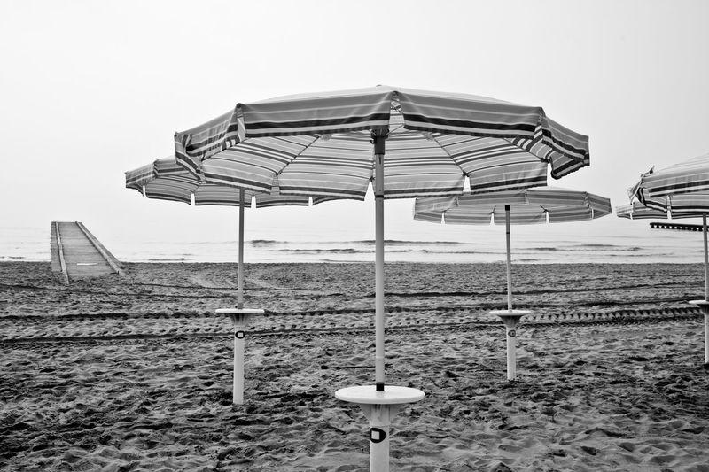 Parasols At Sandy Beach Against Sky