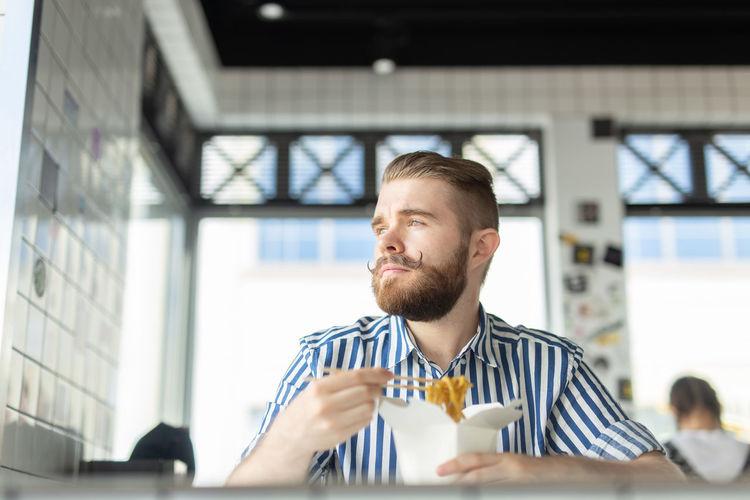 Portrait of man holding ice cream on table
