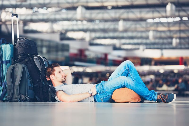 Traveler waiting at the airport departure area for his delay flight. Airport Airport Terminal Airport Waiting Bag Bored Day Dreaming Departure Flying Handsome Journey Luggage Lying Down Men Passenger People Real People Sleepy Thinking Tired Travel Traveler Traveling Trip Waiting Young Adult