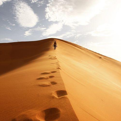 Man walking on sand dune in desert against sky