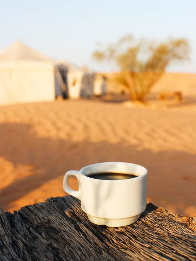 Close-up of coffee cup on sand