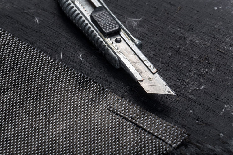 Close-up of utility knife with carbon fiber on workbench