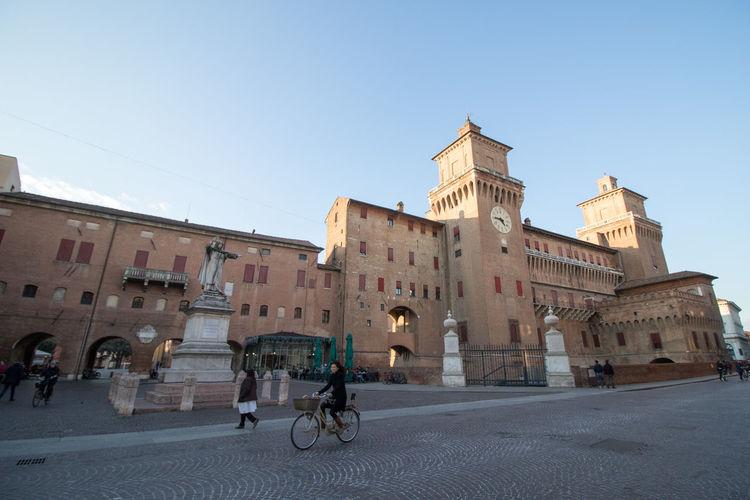 People on street by castello estense against sky