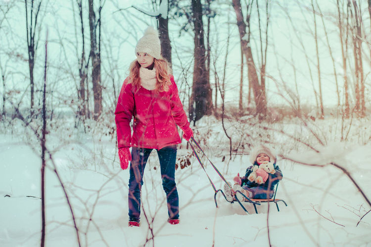 Mother and daughter wearing warm clothing playing in snow during winter