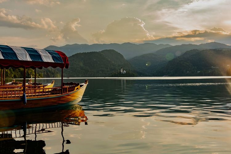 Water Nautical Vessel Mountain Transportation Mode Of Transportation Sky Lake Beauty In Nature Reflection Scenics - Nature Mountain Range Nature Waterfront Cloud - Sky Tranquility Moored Tranquil Scene Non-urban Scene No People Outdoors