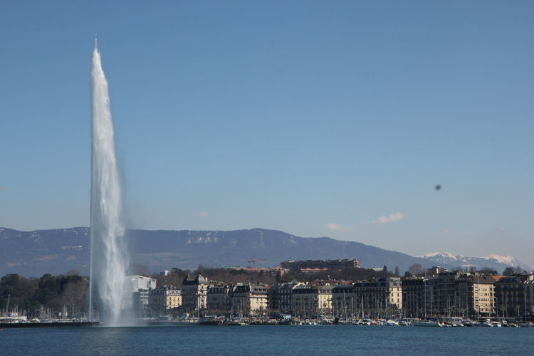 Waterfront scenic view of fountain in city against sky