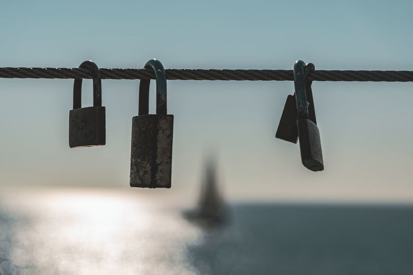 Hanging Metal Padlock Lock Water Sky No People Safety Close-up Hope - Concept Protection Security Nature Day Love Lock Railing Love Positive Emotion Sea Outdoors Horizon Over Water