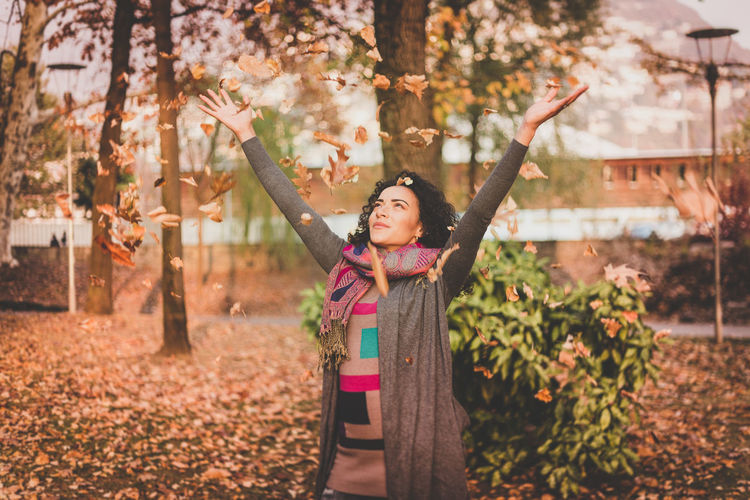 Smiling Young Woman Throwing Autumn Leaves While Standing At Park