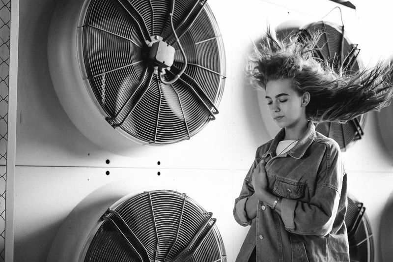 Teenage girl standing against exhaust fans