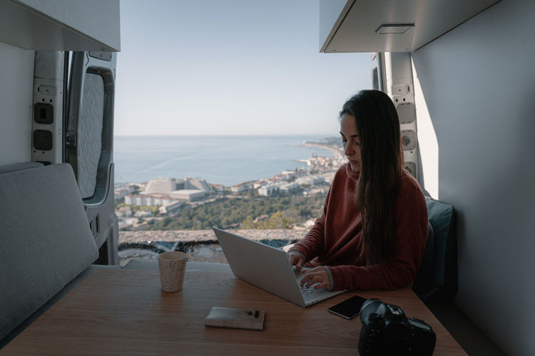 Woman sitting at table working with laptop in vehicle