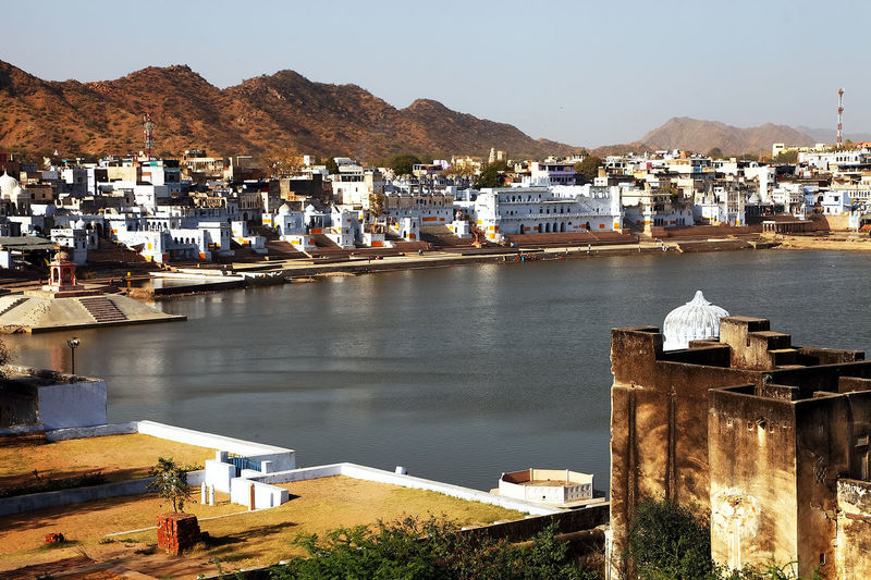 High Angle View Of Lake Amidst Houses By Mountains In Pushkar