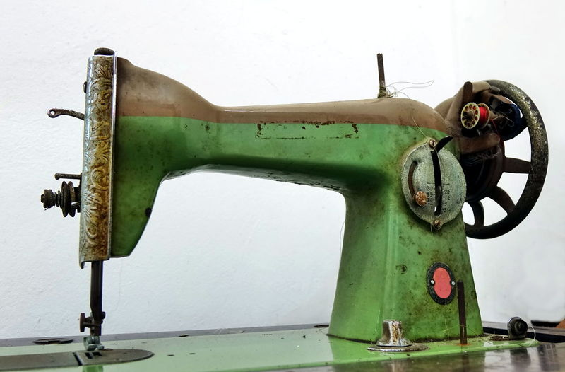 An old vintage sewing machine that is no longer functional Corrosion Obsolete Wheel Antique Equipment Green Color Iron - Metal Machinery Patina Rusty Sewing Machine Sewing Needle Technology Weathered