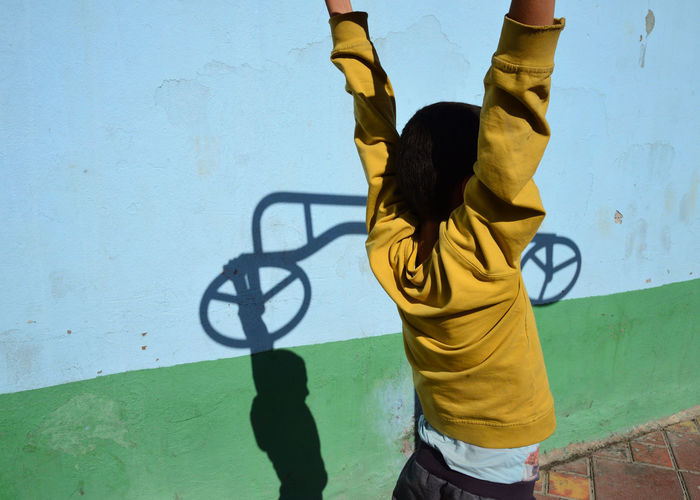 Rear view of girl standing with arms raised by wall