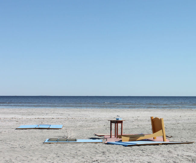 Deck Chairs On Beach Against Clear Blue Sky