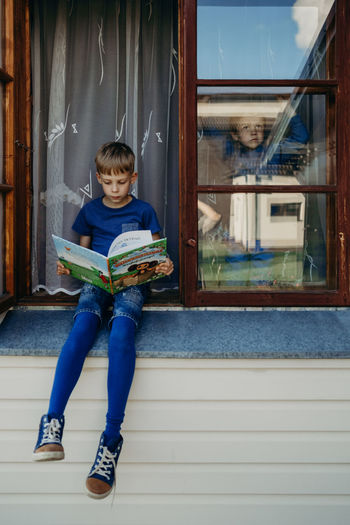 Reading The Portraitist - 2018 EyeEm Awards The Week on EyeEm Book Brothers Child Childhood Lifestyles Portrait Sky Summer Window The Portraitist - 2018 EyeEm Awards