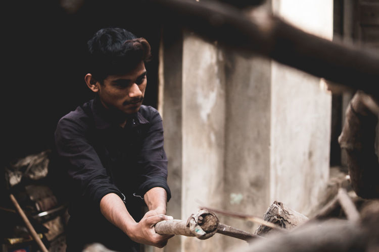 Boy cutting wood with axe
