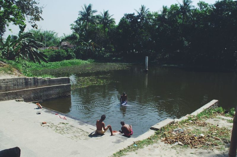D A I L Y C H O R E S, Men busy in their daily chores; bathing, washing clothes and enjoying the rich sunshine, outside a temple premises in the state of Bihar, India. Bath Beauty In Nature Bright Eye4photography  EyeEm Best Shots EyeEm Nature Lover Green Color Hello World Incredible India Light And Shadow Nature Outdoors Peaceful People Pond Rural Scene Shadow Sitting Stairs Sunny Day Taking Photos Tranquility Trees Village Water The Street Photographer - 2017 EyeEm Awards The Street Photographer - 2017 EyeEm Awards The Week On EyeEm An Eye For Travel
