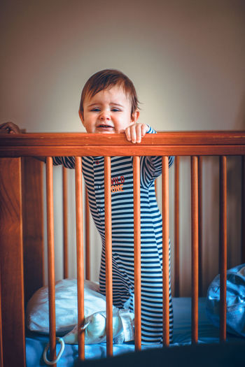 Portrait of cute baby boy standing in crib at home