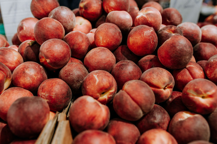 Food And Drink Food Healthy Eating Fruit Freshness Wellbeing Large Group Of Objects No People Outdoors Repetition Focus On Foreground Day Container Red Abundance Still Life Close-up Selective Focus Market Ripe Peach Peaches Peach Color Freshness Market Stall Market