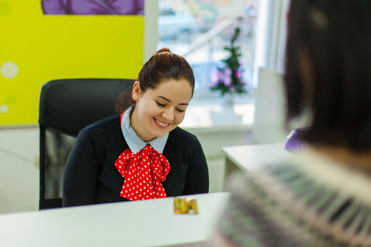 High angle view of smiling hotel receptionist with eyes closed