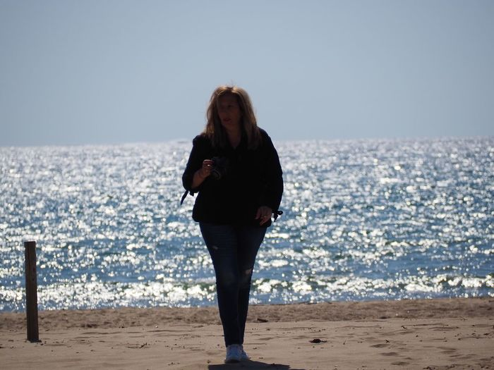 Full length of woman walking at beach against clear sky
