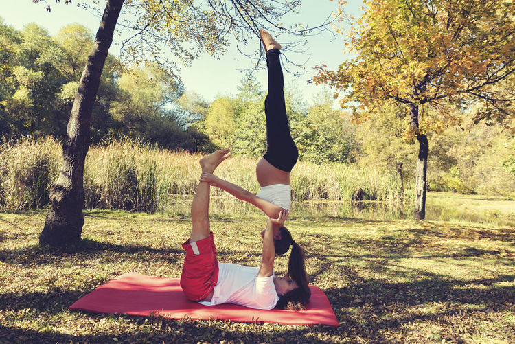 Pregnant woman and a man upside down in a acro yoga practice. Selective focus Autumn Couple Exercise Man Practice Relaxing Woman Yoga Activity Balance Belly Caucasian Healthy Lifestyle Heterosexual Couple Lake Leisure Activity Nature Outdoors Park Partner Pregnancy Pregnant Smiling Sport Togetherness
