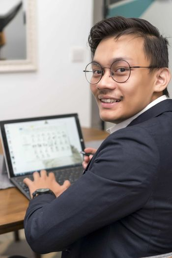 Asian malay man working at home with laptop smiling to the camera Smiling Eyeglasses  Glasses Portrait Real People One Person Technology Indoors  Looking At Camera Happiness Communication Connection Wireless Technology Young Adult Adult Men Males  Business Person Well-dressed