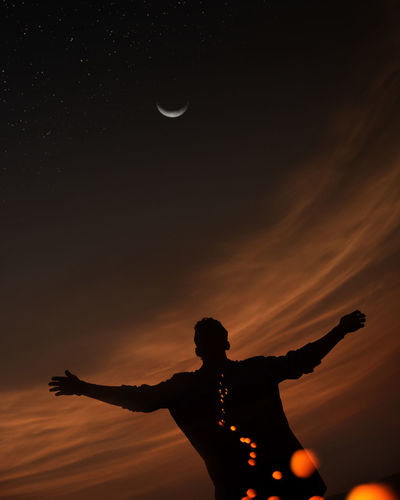 Silhouette man with arms outstretched against sky at sunset