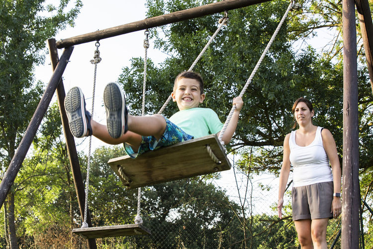 Boy enjoying swing by mother at park