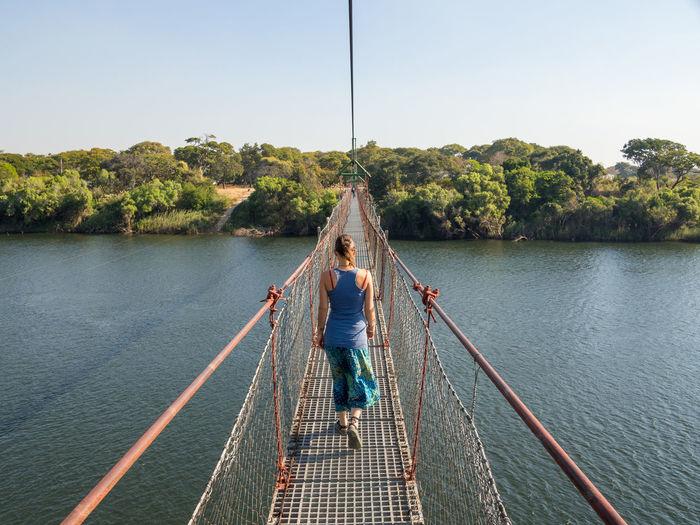 Rear view of youg woman walking on footbridge over river zambezi at chinyingi, zambia