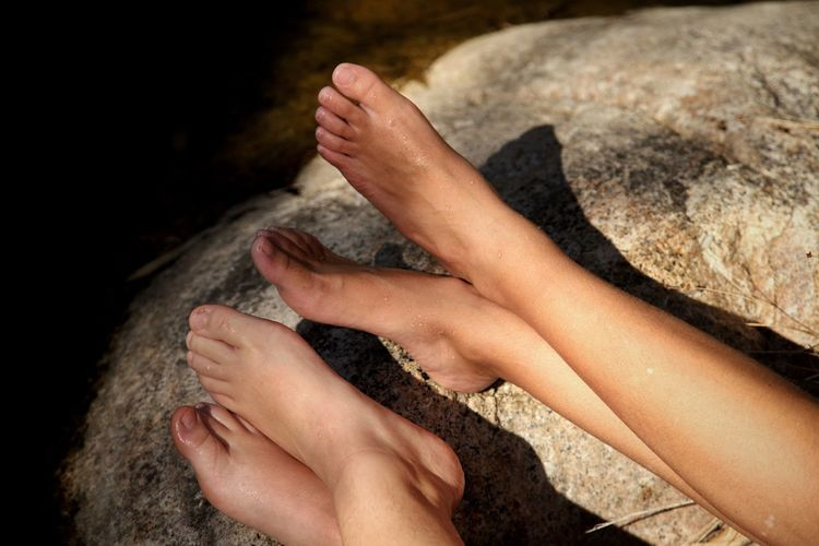 Midsection of woman hand on rock