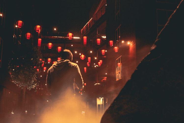 Rear View Of Man On Illuminated City At Night