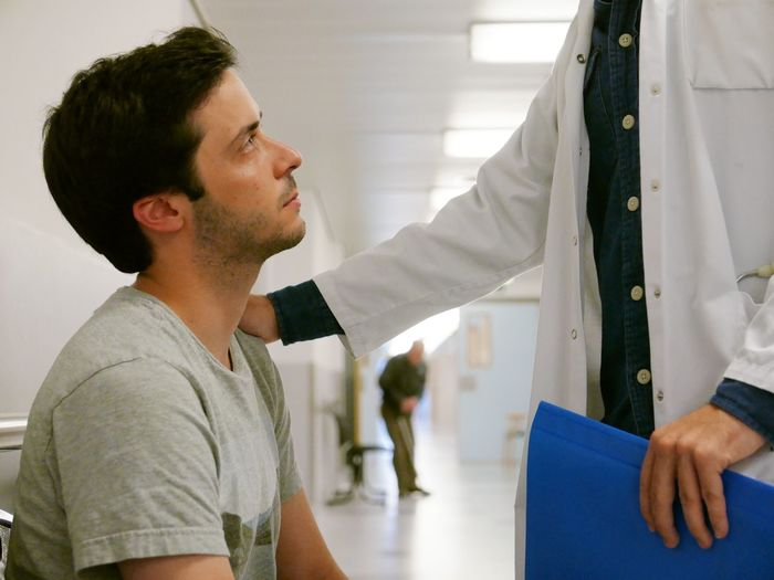 Midsection Of Doctor Comforting Man In Hospital
