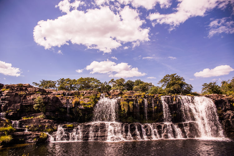 View of waterfall against cloudy sky