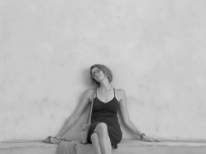 Fashion model sitting against wall