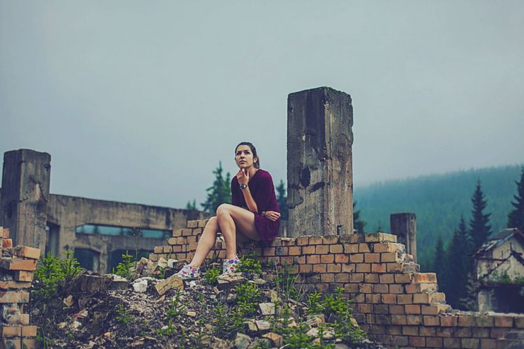 Thoughtful woman sitting on brick wall of abandoned building