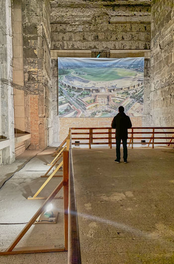 Rear view of man looking through wall