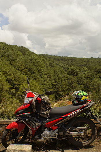 Adventure Beauty In Nature Cloud - Sky Day Extreme Sports Growth Helmet Land Vehicle Landscape Mode Of Transport Motorcycle Motorcycle Racing Mountain Nature No People Outdoors Sky Stationary Transportation Tree