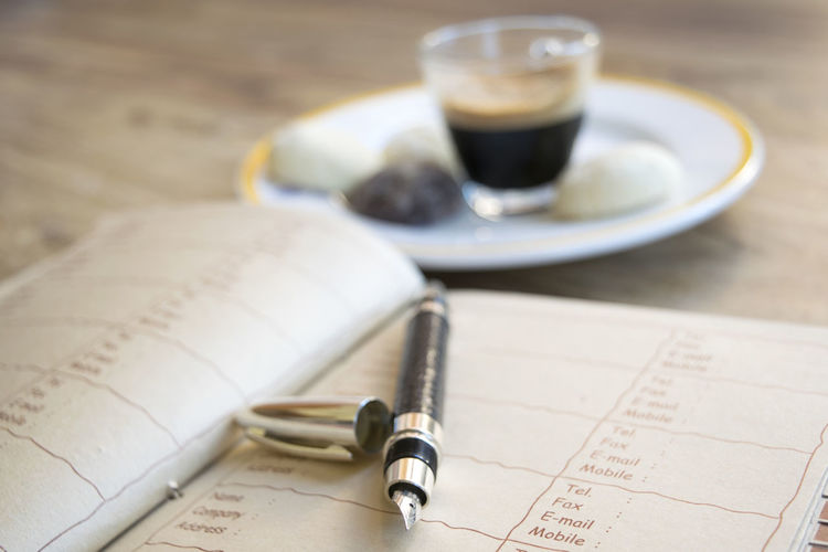 Close-up of pen and book with coffee on table