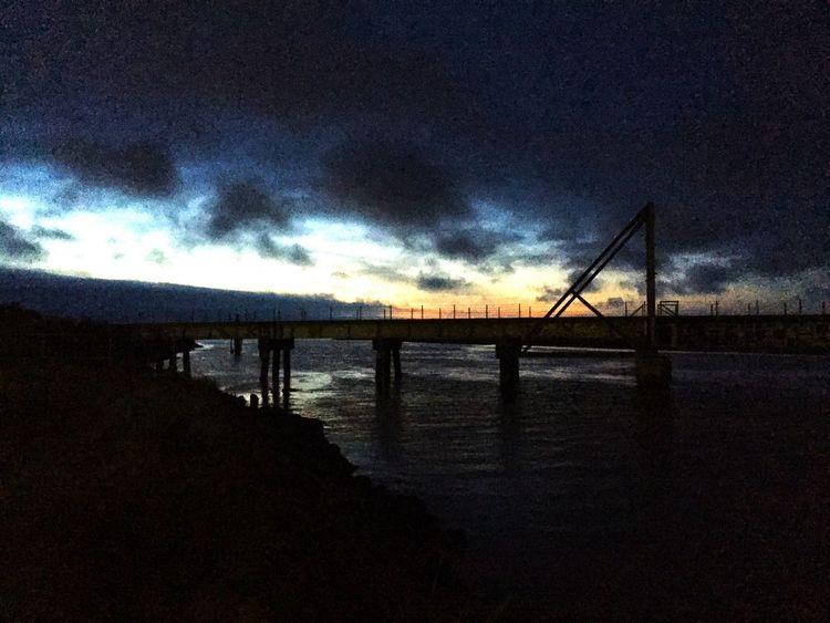 Train bridge over water at night.
