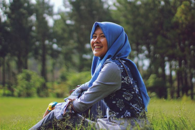 Portrait of smiling young woman wearing hijab sitting on land
