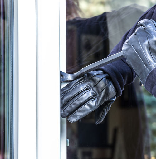 a burglar tries to break into a house Security Break Burglar Burglary Casual Clothing Close-up Criminal Day Focus On Foreground Glass - Material Glove Hand Holding Human Body Part Human Hand Lifestyles Midsection One Person Outdoors Real People Reflection Robber Thief Transparent Window