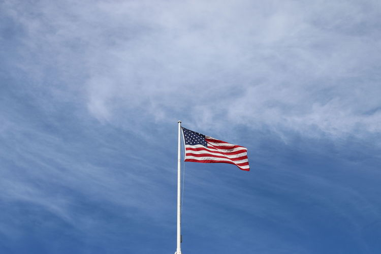 Low angle view of flag against cloudy sky
