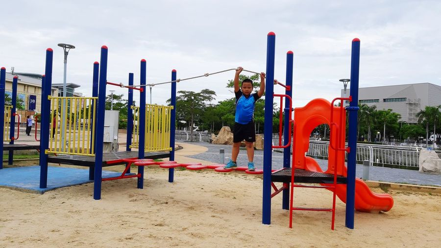 Boy playing on playground against sky