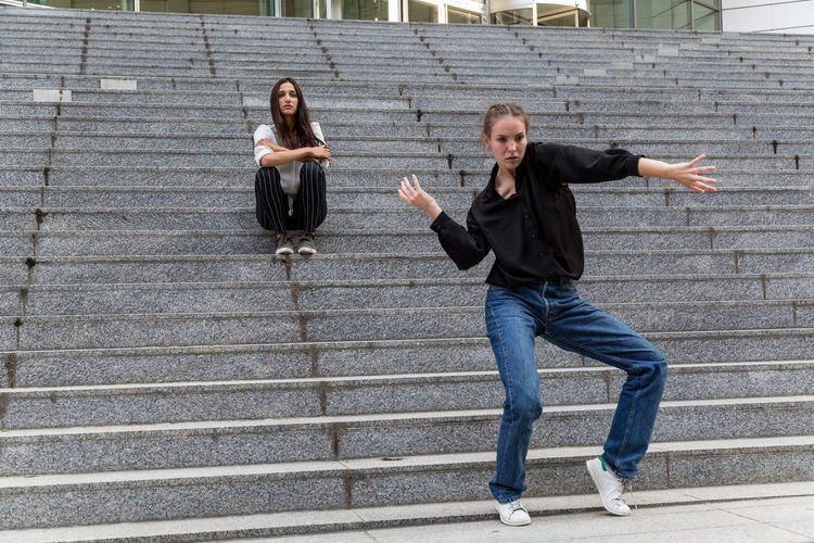 Young woman dancing and another sitting by an outdoor staircase Steps And Staircases Full Length Young Women Staircase Front View Two People Brown Hair Real People Jeans Casual Clothing Dancing Sitting Caucasian Mixed Race Person Indian Culture  Outdoors Day Women Young Adult Dance Pose