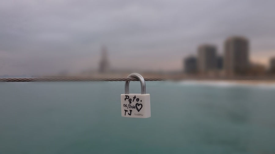Text On Padlock Hanging On Wire Rope By Lake In City